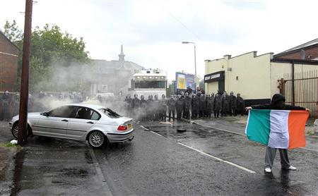 A nationalist youth displays the Irish National Flag beside a burnt-out car and riot police after trouble erupted in the Ardoyne area of North Belfast, Northern Ireland July 12, 2012. REUTERS/Cathal McNaughton