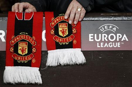 A Manchester United supporter adjusts a club scarf before their Europa League second leg round of 32 soccer match against Ajax at Old Trafford in Manchester, northern England, February 23, 2012. REUTERS/Phil Noble