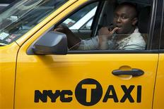 A New York City taxi driver looks out of his window as he drives through Times Square in New York, July 12, 2012. REUTERS/Keith Bedford