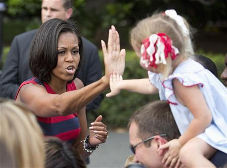 First Lady Michelle Obama high-fives a child during Independence Day celebrations on the South Lawn of the White House in Washington July 4, 2012. REUTERS/Joshua Roberts