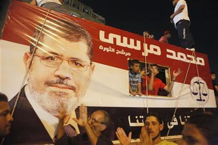 A picture of Egypt's President Mohamed Mursi is seen on a vehicle as his supporters gather at Tahrir square in Cairo in this July 10, 2012 file photo. REUTERS/Asmaa Waguih