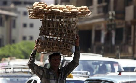 A man carries bread on wooden racks to be sold to customers in Cairo July 2, 2012. REUTERS/Amr Abdallah Dalsh