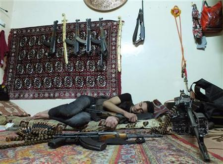 A member of rebel group Khaled ibin al Walid Fighters rests next to weapons in a temporary house used by rebels at Hamidiyeh district in the central city of Homs July 1, 2012. REUTERS/Yazen Homsy