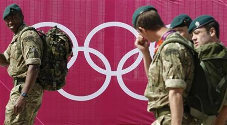 Marines pass the Olympic rings outside the London 2012 Olympic Park at Stratford in London July 12, 2012. REUTERS/Luke MacGregor