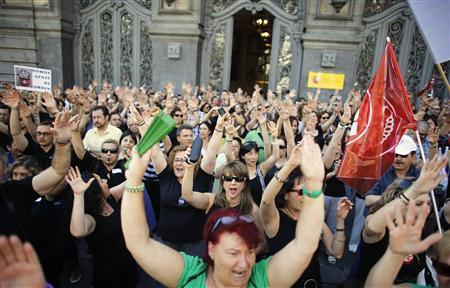 Civil service workers raise their arms during a protest against government austerity measures outside the Education Ministry in Madrid July 13, 2012. REUTERS/Paul Hanna