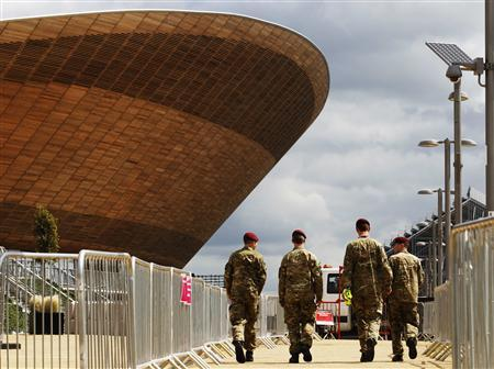 Soldiers walk past the Velodrome at the London 2012 Olympic Park in Stratford, east London July 13, 2012. REUTERS/Luke MacGregor