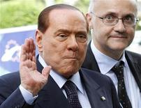 Italy's former Prime Minister Silvio Berlusconi (L) waves as he arrives for a meeting of the European People's Party (EPP), ahead of a two-day European Union leaders summit, in Brussels June 28, 2012. REUTERS/Sebastien Pirlet
