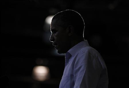 U.S. President Barack Obama is silhouetted during a campaign rally at Phoebus High School in Hampton, Virginia, July 13, 2012. REUTERS/Jason Reed