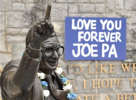 Signs and flowers are seen at the statue of the late Penn State football coach Joe Paterno, before the annual Spring football scrimmage in State College, Pennsylvania April 21, 2012. REUTERS/Pat Little