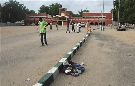 People walk in front of a mosque after a bomb attack in Nigeria's north-eastern city of Maiduguri July 13, 2012. REUTERS/Olatunji Omirin
