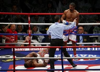 Britain's David Haye (R) looks down at opponent Dereck Chisora after scoring a fifth round knockout in their fight for the vacant WBO and WBA International Heavyweight Championship at Upton Park in London July 14, 2012. REUTERS/Eddie Keogh