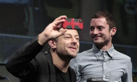 Cast member Elijah Wood (R) watches co-star Andy Serkis at the beginning of a panel for the film ''The Hobbit: An Unexpected Journey'' during the Comic Con International convention in San Diego, California July 14, 2012. REUTERS/Mario Anzuoni