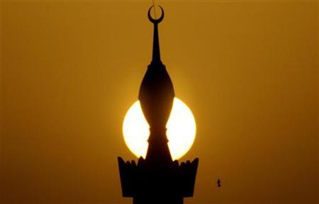The sun sets behind a minaret in the centre of Riyadh March 1, 2008. REUTERS/Ali Jarekji/Files