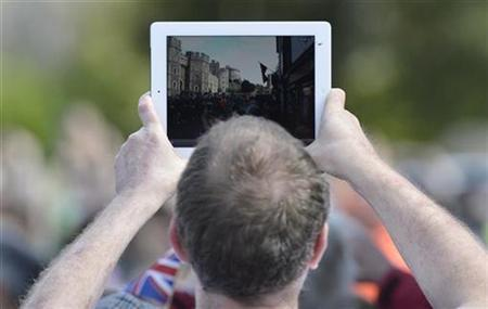 A member of the public uses his tablet computer to film as Britain's Queen Elizabeth takes part in a walkabout from Windsor Castle to the Guildhall in Windsor in southern England April 30, 2012. REUTERS/Toby Melville