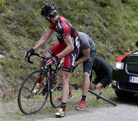 BMC Racing Team rider Cadel Evans of Australia receives assistance after a flat tyre during the 14th stage of the 99th Tour de France cycling race between Limoux and Foix, July 15, 2012. REUTERS/Fred Mons/Pool