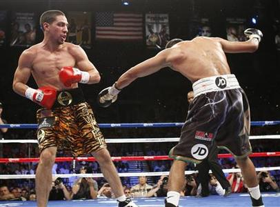 WBC champion Danny Garcia (L) of the U.S. looks on as Amir Khan of Britain falls to the canvas during their WBC/WBA 140 pound championship fight at the Mandalay Bay Events Center in Las Vegas, Nevada July 14, 2012. REUTERS/Steve Marcus