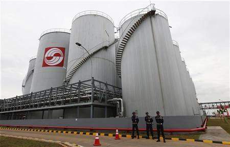 Security officers stand guard in front of palm oil storage tanks at the palm oil-based refinery plant owned by Sinar Mas Agro Resources and Technology (SMART) in Marunda, West Java March 30, 2011. REUTERS/Enny Nuraheni