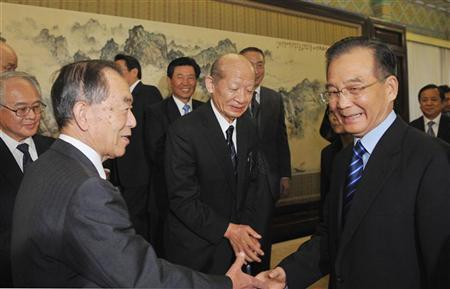 Japan's Ambassador to China Uichiro Niwa (L) shakes hands with China's Premier Wen Jiabao (R), after their meeting in Beijing October 22, 2011. Taizo Nishimuro, chief Japanese member of the new 21st Century Committee, is seen in the centre. REUTERS/Kota Kyogooku/Pool
