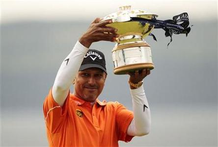 Jeev Milkha Singh holds up the winners trophy during a presentation after winning the Scottish Open golf tournament after an extra hole play off against Italy's Francesco Molinari at Castle Stuart golf course near Inverness, Scotland July 15, 2012. REUTERS/David Moir