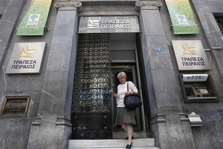 A woman walks out of a Piraeus bank branch in central Athens in this May 30, 2012 file photo. REUTERS/John Kolesidis/Files