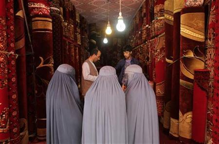 Afghan women talk to a carpet vendor in his shop in Kabul July 8, 2012. REUTERS/Mohammad Ismail