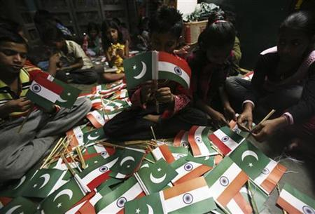 Children of slum dwellers tie India and Pakistan national flags at a workshop run by a non-governmental organisation (NGO) in March 28, 2011. REUTERS/Ajay Verma/Files