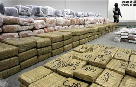 A soldier stands guard next to packages containing marijuana found in a tunnel under the Mexico-U.S. border in Tijuana November 30, 2011. REUTERS/Jorge Duenes
