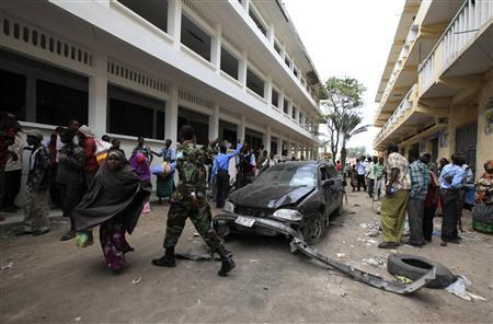 People gather at the scene of a suicide car comb attack in the Hamarwayne district of Somalia's capital Mogadishu, July 16, 2012. REUTERS/Omar Faruk