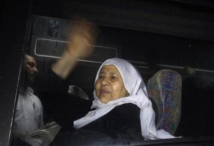 The mother of a Palestinian prisoner on her way to visit her son jailed in Israel waves from inside a bus as it leaves Gaza City July 16, 2012. REUTERS/Ibraheem Abu Mustafa