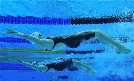Swimmers compete in the women's 200m backstroke heats at the British Gas Swimming Championships 2012 at the Olympic Aquatics Centre in London in a March 8, 2012 file photo. While most spectators at London's Aquatics Centre will be watching the swimmers and the clock to see whether records are being set in the 50 meter pool, engineers and scientists will have their eyes on the lane dividers. If the hundreds of discs are spinning like mad, expect history to be made. REUTERS/Toby Melville/File