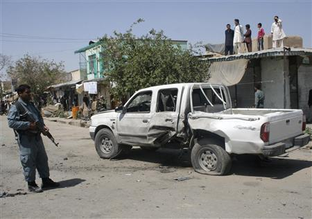 An Afghan policeman stands guard near the bomb-damaged vehicle of the district chief of Khan Abad in Kunduz province July 16, 2012. The chief was not in the vehicle when a magnetic bomb blew up on Monday, but the blast killed a bodyguard and wounded eight civilians, police said. The attack was the third on senior government officials in as many days. REUTERS/Wahdat
