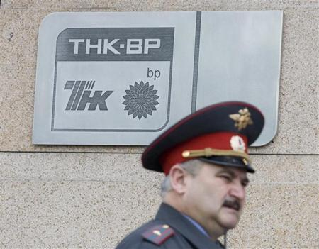 A police officer walks past a plaque of the oil firm TNK-BP at its headquarters in Moscow June 11, 2008. REUTERS/Sergei Karpukhin