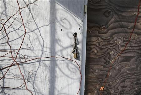 The front door of a home is seen padlocked and boarded up in Brentwood, New York February 10, 2012. REUTERS/Shannon Stapleton
