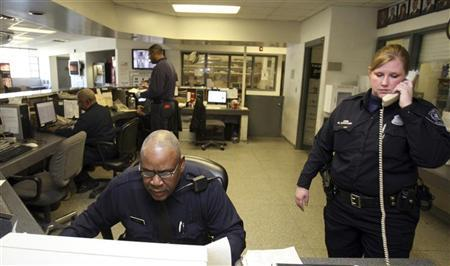 Detroit Police Officers work behind the front desk at the Northeastern District police station in Detroit, Michigan, January 6, 2012. REUTERS/Rebecca Cook
