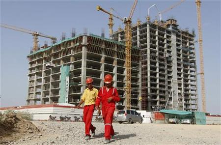 Workers walk in front of a multi-story commercial building under construction on the outskirts of Ahmedabad May 31, 2012. REUTERS/Amit Dave