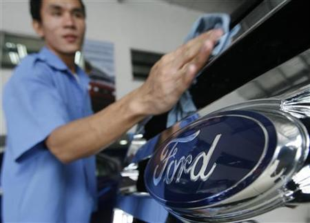 A worker waxes a car in a Ford automobile showroom in Manila June 28, 2012. REUTERS/Cheryl Ravelo