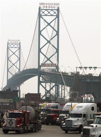 Transport trucks move slowly across the Ambassador Bridge into Detroit, Michigan from Windsor, Ontario, Canada in this March 19, 2003 file photo. REUTERS/Rebecca Cook/Files