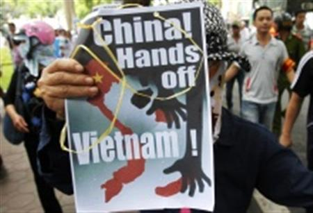 A protester holds an anti-China placard as she marches during a demonstration along a street in Hanoi July 8, 2012. REUTERS/Stringer