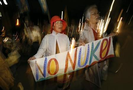 Protesters march with an anti-nuclear banner at a rally against a possible restart of nuclear reactors in Tokyo June 6, 2012. REUTERS/Kim Kyung-Hoon/Files