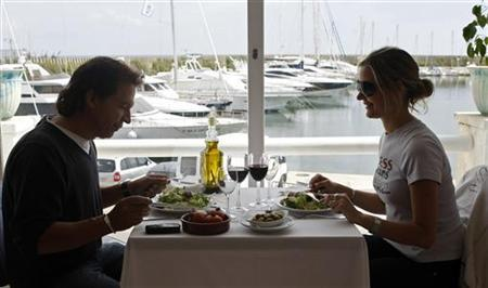 A man and a woman have lunch at a restaurant at the port of El Masnou, near Barcelona, May 16, 2008. REUTERS/ Albert Gea