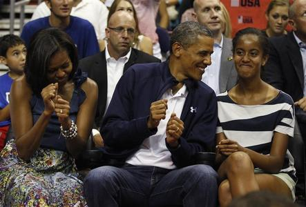 President Barack Obama and first lady Michelle Obama (L) move to the music as daughter Malia (R) looks on as they attend the Olympic men's exhibition basketball game between Team USA and Brazil in Washington July 16, 2012. REUTERS/Kevin Lamarque