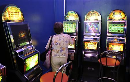 A woman plays on a slot machine in a bingo hall in downtown Rome July 6, 2012. REUTERS/Max Rossi