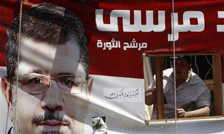 A supporter of Egypt's first Islamist President Mohamed Mursi shouts slogans against military rules and members of Mubarak's regime from a vehicle with an image of Mursi, in front of Egypt's state council in Cairo July 17, 2012. REUTERS/Amr Abdallah Dalsh
