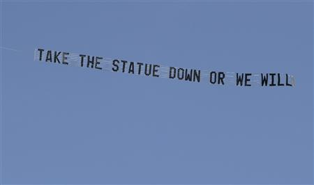 An airplane tows a banner that reads ''Take the Statue Down or We Will'' as it flies over the Penn State campus in State College, Pennsylvania July 17, 2012. REUTERS/Nabil K. Mark/Centre Daily Times