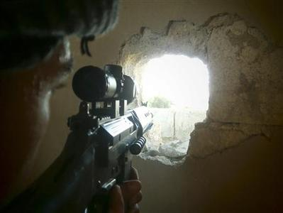 A member of the Free Syrian Army points his weapon through a hole in a wall as he takes up a defense position in a house in Qusseer neighbourhood in Homs July 16, 2012. REUTERS/Shaam News Network/Handout