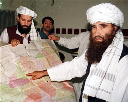 Jalaluddin Haqqani (R) points to a map of Afghanistan during a visit to Islamabad, Pakistan while his son Naziruddin (L) looks on in this October 19, 2001 file photograph. REUTERS/Stringer/Files