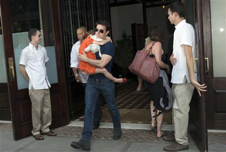 Actor Tom Cruise carries his daughter Suri as they make their way from a hotel in New York, July 17, 2012. REUTERS/Keith Bedford