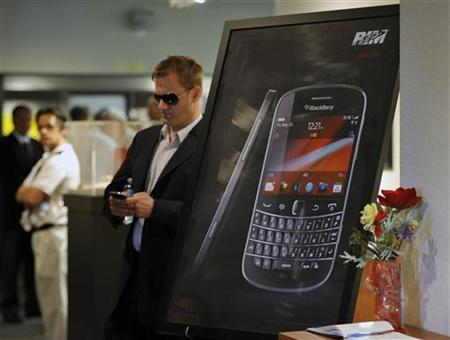A guest checks his mobile device before the start of the Research In Motion Limited (RIM) annual general meeting of shareholders in Waterloo July 10, 2012. REUTERS/ Mike Cassese
