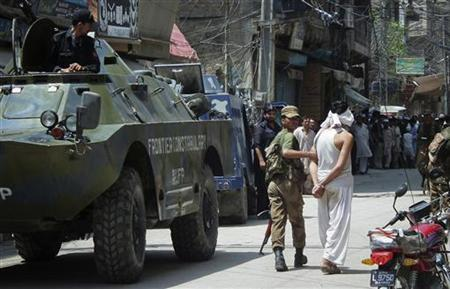 A paramilitary soldier detains a man at the scene of a gunmen attack on a police station in Bannu, northwest Pakistan July 16, 2012. REUTERS/Zahid Mohammad