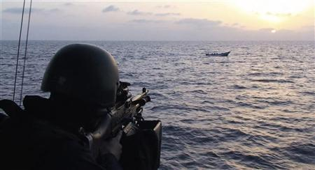 A soldier aboard the Swedish corvette HMS Malmo aims his machinegun at a boat carrying suspected pirates in the Gulf of Aden May 26 2009. REUTERS/Sgt. Mats Nystrom/Combat Camera Swedish Armed Forces/Scanpix